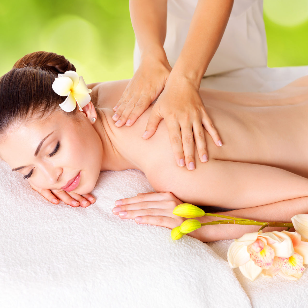 Woman having massage of body in the spa salon over green nature background